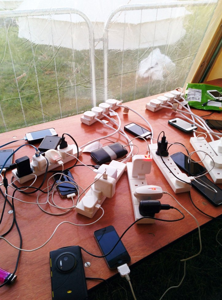 Still plugged into the Matrix. Campers charging their mobile phones at Rapha Tempest. Photo © Zarina Holmes / GLUE